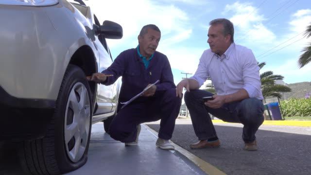 vídeos y material grabado en eventos de stock de macho adulto hablando con un mecánico para arreglar el neumático - américa del sur