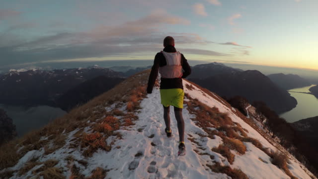 Adult male trail runs on snowy mountain ridge above lake at sunset