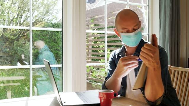 взрослый мужчина в маске для лица, работает из дома и сидит перед ноутбуком, показывающим документы во время конференц-звонка. - covid testing стоковые видео и кадры b-roll