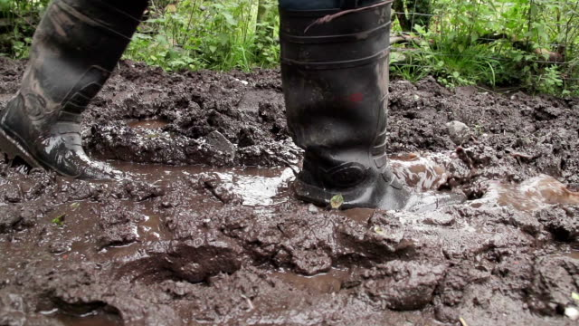 maschio adulto con wellies sul terreno fangoso - fare un passo video stock e b–roll