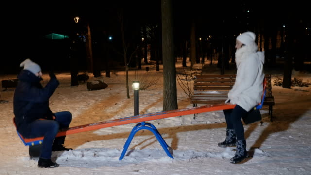 Adult man and woman swings on a seesaw in evening winter park video