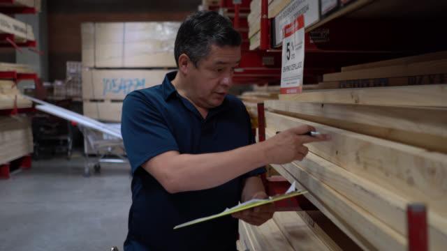vídeos y material grabado en eventos de stock de hombre adulto en un almacén de madera haciendo el conteo de inventario y escribir todo usando un portapapeles y un bolígrafo - material de construcción