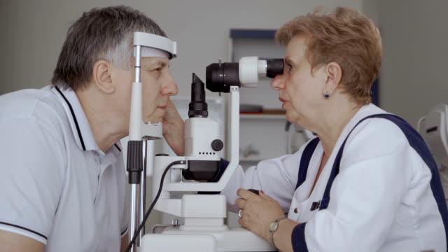 vidéos et rushes de homme adulte vérifier sa vue avec des équipements optiques spéciaux - réfracteur