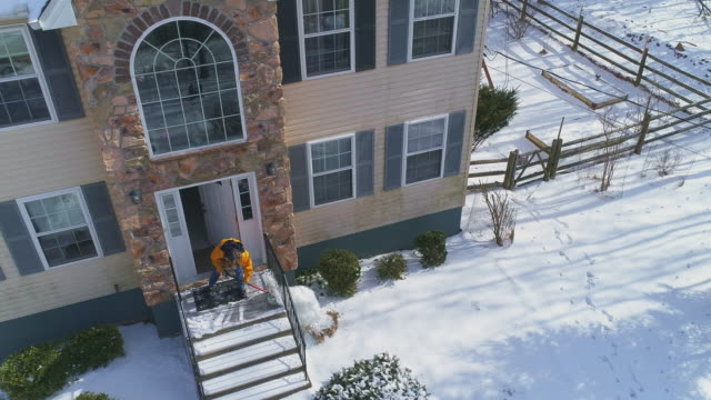 Adult man cleaning the porch from the snow after a winter snowfall.