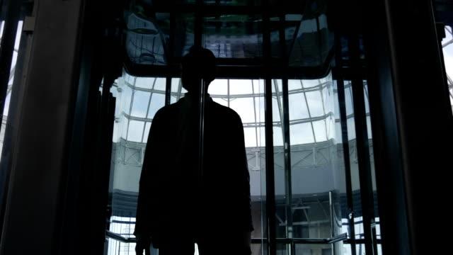 uomo adulto che fuori dall'ascensore - scala mobile video stock e b–roll