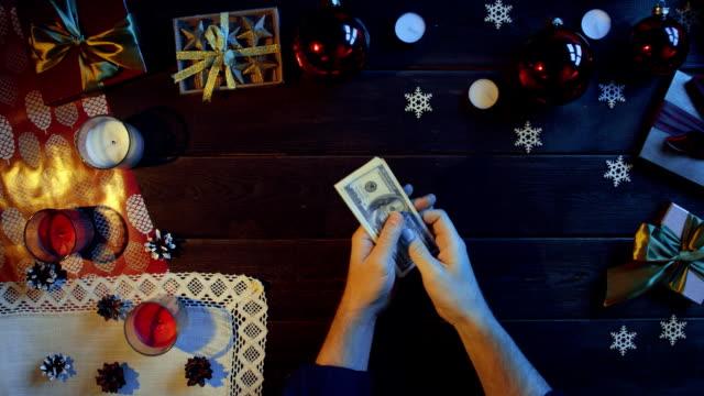 成人男性の新年装飾テーブル、ショットをトップダウンで現金を数える ビデオ