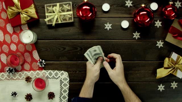 成人男性がクリスマス装飾テーブル、ショットをトップダウンで現金を数える ビデオ