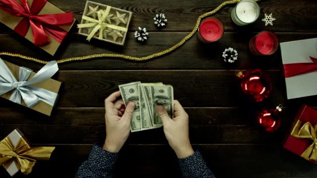 成人男性がクリスマス装飾デスク、ショットをトップダウンで現金お金をカウントします。 ビデオ