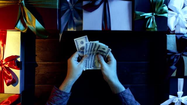 成人男性がクリスマス装飾テーブル、ショットをトップダウンで現金お金をカウントします。 ビデオ