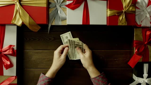 成人男性がクリスマス装飾テーブル、ショットをトップダウンでドルをカウントします。 ビデオ