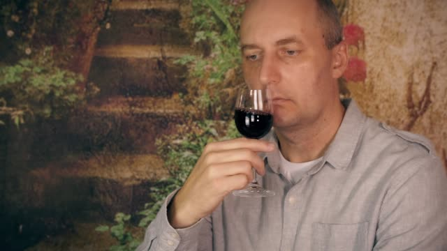 Adult man drinking red wine from glass and enjoy good taste close up video
