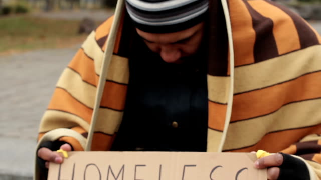 Adult man holding homeless please help sign, poverty, social vulnerability video
