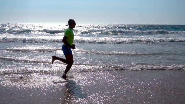 Adult Man in Shorts with a T-shirt Jogging on Ocean Beach video