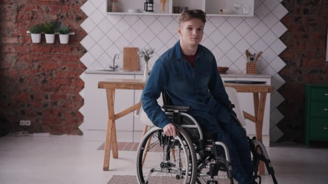 Adult man in sitting wheelchair at cozy house Young and disabled man wearing in denim or jeans clothes and spending day at home with bright cozy room with modern interior. Male looking at camera and sitting in special comfort wheelchair persons with disabilities stock videos & royalty-free footage