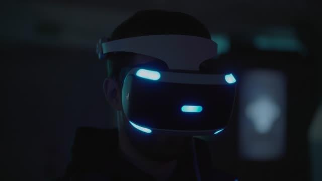 yetişkin adam başa takılı ekran karanlık odada sergi görüntülemek için kullanarak - sanal gerçeklik stok videoları ve detay görüntü çekimi