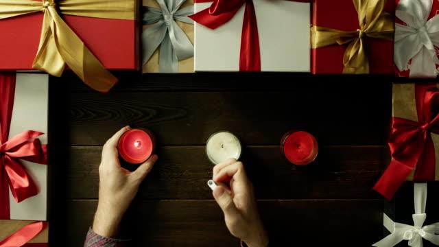 成人男性が装飾されたテーブルから、ショットをトップダウンでクリスマスキャンドルをライトします。 ビデオ