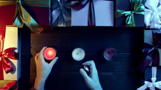 成人男性が装飾テーブル、ショットをトップダウンで新年キャンドルを点灯します。 ビデオ