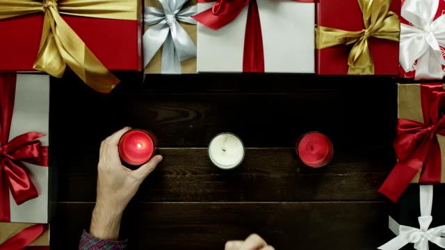 成人男性が装飾されたテーブルから、ショットをトップダウンでクリスマス キャンドルを点灯します。 ビデオ