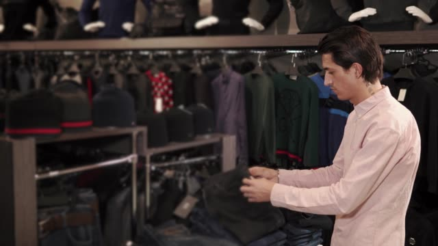 Adult man looking for nice jeans in a shop video