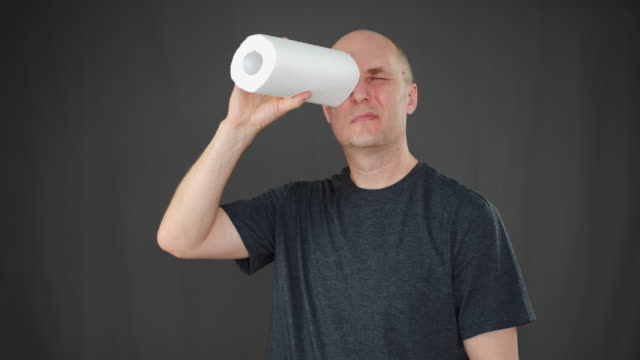 adult man looking through toilet paper like subpipe on black background. man using paper towel like spyglass. people in isolation during coronavirus. covid-19 quarantine. - rotolo video stock e b–roll
