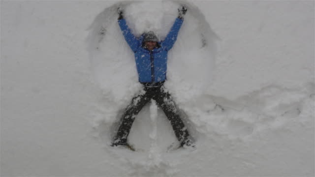 Adult man lying in fresh snow, making snow angels having fun video