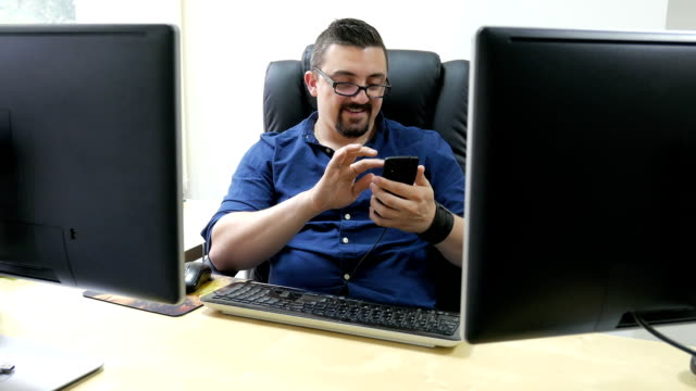 Adult man office manager or worker using his smart phone at the workplace video