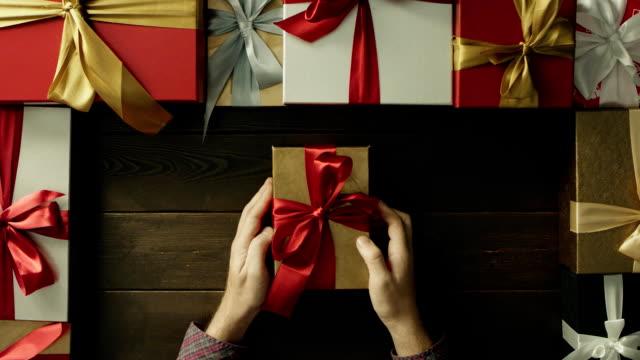 成人男性が装飾された木製のテーブル、トップダウンのショットの中のプラスチック製の解剖学人間の心のクリスマス ギフト ボックスを開きます ビデオ