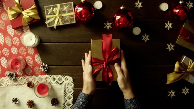 成人男性が装飾された木製のテーブル、トップダウンのショットの内部のプラスチックから作られた本物の人間の心のクリスマス ギフト ボックスを開きます ビデオ