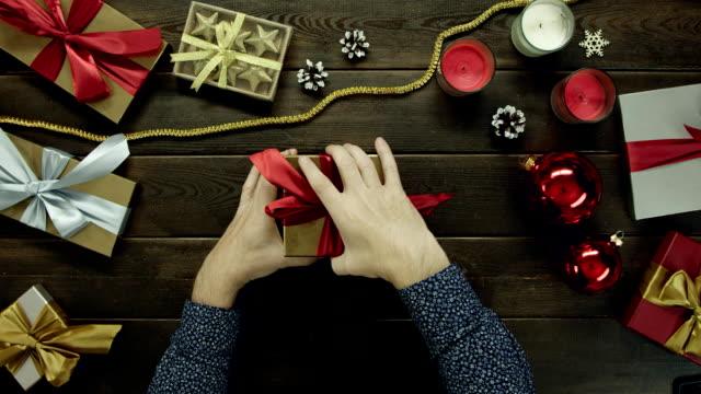 成人男性が質問記号にショットをトップダウンで棒のノートでクリスマス プレゼントを開きます ビデオ