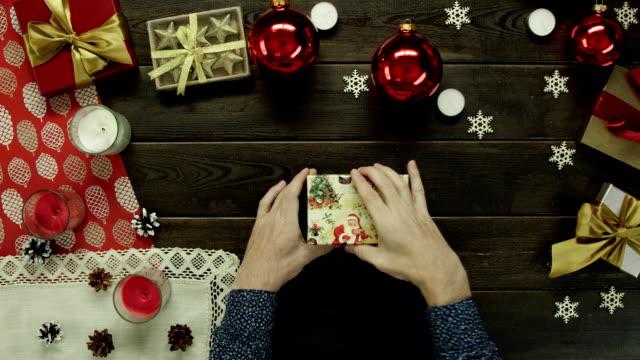 大人の男は内、トップ ショット ダウン ドルでクリスマス プレゼント ボックスを開きます ビデオ