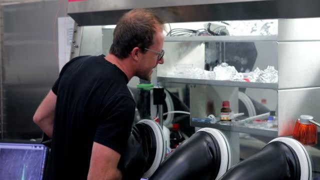 vídeos de stock, filmes e b-roll de homem adulto pesquisador usando luvas para preparar semicondutores orgânicos para análise de fotocorrente - amostra científica