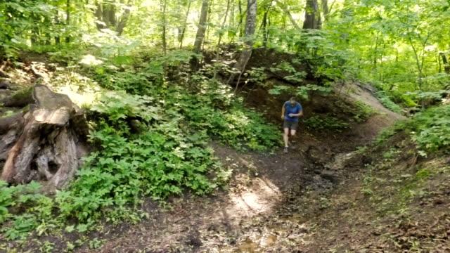 vuxen man kör jogging utomhus i en skog natur på en skogsstig och njuter av det och ser glad - tävlingsdistans bildbanksvideor och videomaterial från bakom kulisserna
