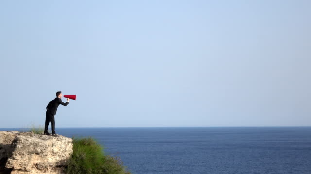 Adult Man Shouting Through Old Fashioned Red Megaphone In Outdoor Color 4K UHD video of adult man wearing a black formal full suit shouting through old fashioned red megaphone in outdoor.The model is seen in full length and standing on the edge of rocky cliff.He is standing by sea shore.The horizon over sea is seen on the background.Shot in daylight with. megaphone stock videos & royalty-free footage