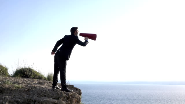 Adult Man Shouting Through Red Megaphone In Outdoor Color 4K UHD video of adult man wearing a black formal full suit shouting through red megaphone in outdoor.The model is seen in full length and standing on the edge of rocky cliff.He is standing by sea shore.The horizon over sea is seen on the background.Shot in daylight with. megaphone stock videos & royalty-free footage
