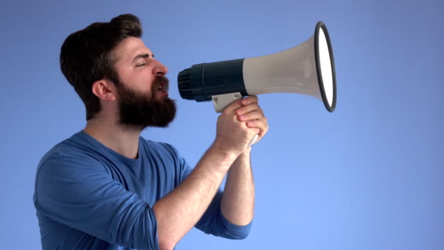 Adult Man Shouting Via White Modern Megaphone 4K video of adult man holding a white modern megaphone and shouting.He is standing in front of blue background.The model is wearing a blue sweater and has beard and brown hair. megaphone stock videos & royalty-free footage