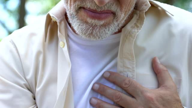 adult man suddenly feeling sharp chest pain, risk of heart attack, cardiology - serce człowieka filmów i materiałów b-roll