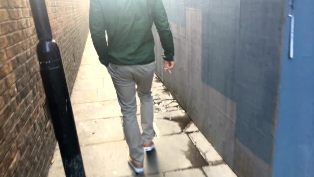 adult man walking down an alley - solo un uomo video stock e b–roll