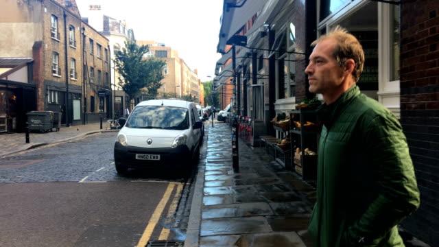 adult man walking on a city street - solo un uomo maturo video stock e b–roll