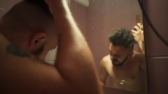 Adult man with a beard cuts his hair in bathroom