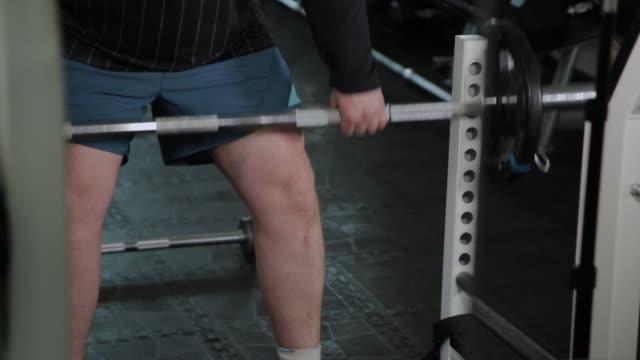 erwachsene mann mit übergewicht führt deadlift in der turnhalle - gewichtstraining stock-videos und b-roll-filmmaterial
