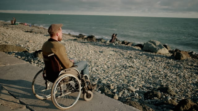 Adult man with paralysis of bottom of body is sitting in sea shore and relaxing - vídeo