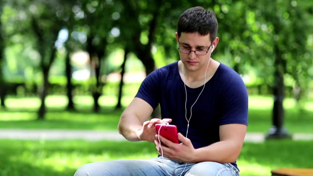 Adult man with red smartphone sits on the bench in public garden video