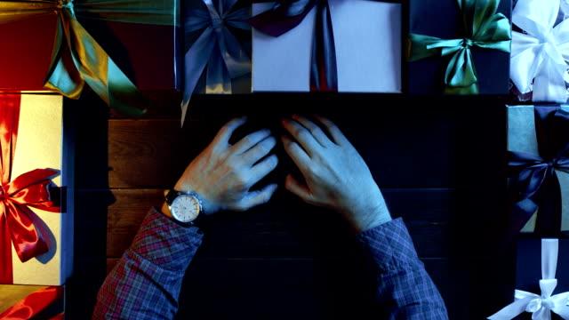 休日クリスマス木製テーブル、ショットをトップダウンで座って手に時計を成人男性 ビデオ
