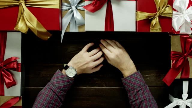 休日正月木製テーブル、ショットをトップダウンで座って手に時計を成人男性 ビデオ
