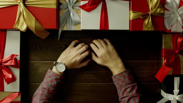 ホリデイ ・木製のテーブル、ショットをトップダウンで座って手に時計を成人男性 ビデオ