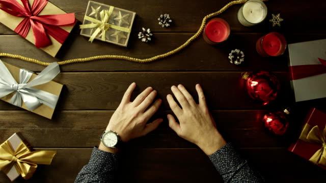 ホリデイ ・木製のテーブル、トップダウンのショットで彼の手を見る大人の男が座っています。 ビデオ