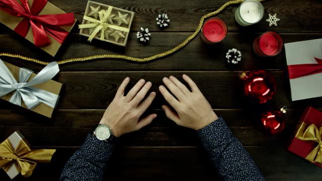 休日クリスマス木製テーブル、トップダウンのショットで彼の手を見る大人の男が座っています。 ビデオ