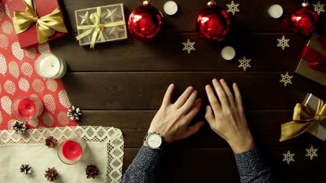 クリスマス、トップダウンのショットの前に飾られた木製のテーブルに座って彼の手で時計を成人男性 ビデオ