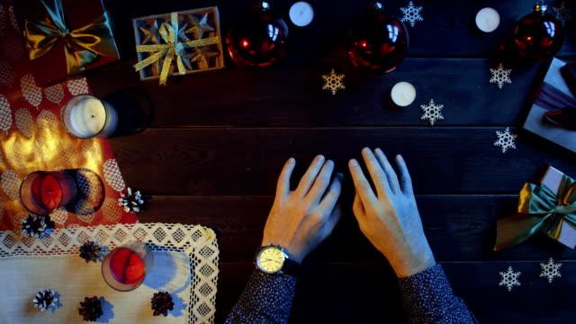 新しい年、トップ ショット ダウンする前に飾られた木製のテーブルのそばに座って彼の手で時計を成人男性 ビデオ
