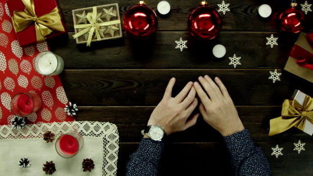 クリスマス、トップ ショット ダウン前に飾られた木製のテーブルに座って彼の手で時計を成人男性 ビデオ